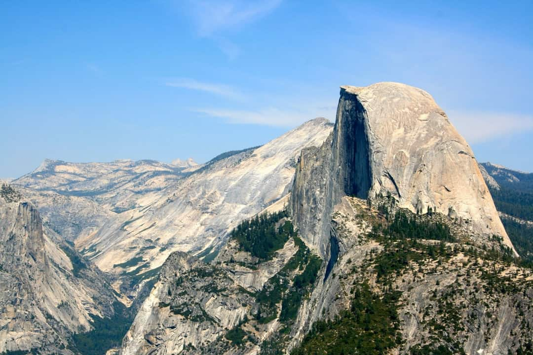A view of a snow covered mountain with Half Dome in the background