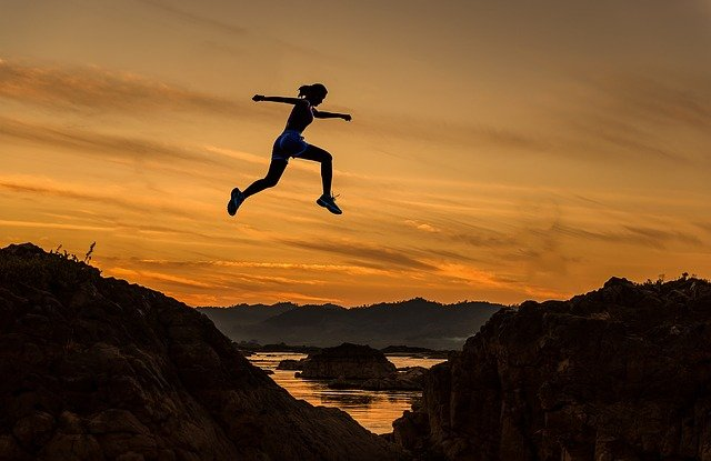 A man flying through the air on top of a mountain